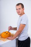 Handsome man with knife carving pumpkin Jack-O-Lantern for Hallo Royalty Free Stock Image