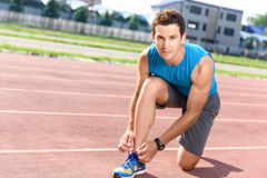 Handsome man lacing his sneakers Stock Photos