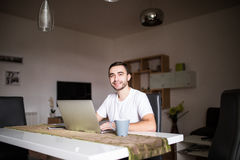 Handsome man with laptop and coffee cup in the kitchen mornings Stock Photos