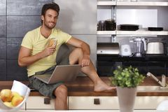 Handsome man with laptop in kitchen Royalty Free Stock Image