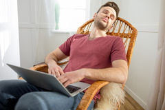 Handsome man with laptop sleeping in rocking chair Stock Photos
