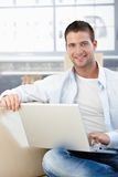 Handsome man with laptop smiling on sofa Royalty Free Stock Photography