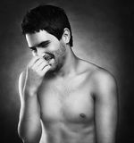 Handsome man laughing while covering his mouth with on a dark ba Royalty Free Stock Photography