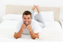 Handsome man laughing lying on his bed Royalty Free Stock Images