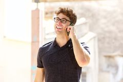 Handsome man laughing and talking on mobile phone Stock Photo