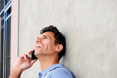 Handsome man laughing and talking on mobile phone. Portrait of handsome man laughing and talking on mobile phone stock photo