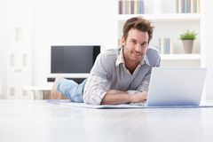 Handsome man laying on floor at home smiling Stock Photo
