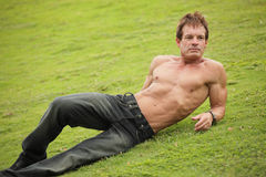 Handsome man laying on the grass Royalty Free Stock Images