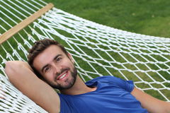 Handsome man laying in hammock and smiling.  Royalty Free Stock Images