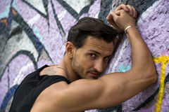 Handsome man leaning against graffiti wall Royalty Free Stock Photography