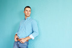 Handsome man leaning against a turquoise wall. Looking out the window Royalty Free Stock Photography