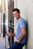 Handsome man leaning against wall outside with mobile phone. Side portrait of handsome man leaning against wall outside with mobile phone stock photography