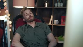 Handsome man leaning back from computer. Employee falling from broken chair stock footage