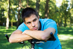 Handsome man leaning on a bicycle Stock Photos