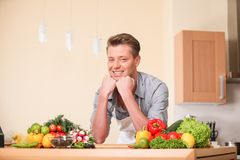 Handsome man leaning on chopping board. Stock Images