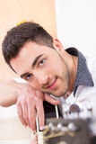 Handsome man  leaning on his guitar and smiling Stock Photos