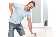 Handsome man leaning on sofa and feeling pain. Royalty Free Stock Photography