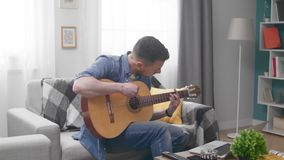 Handsome man learns to play the guitar with the help of an online tutorial