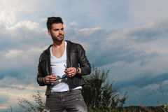 Handsome man in leather jacket holding sunglasses. Looks to side in the outdoors Stock Photography