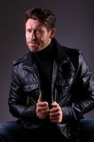 Handsome man in leather jacket seated Royalty Free Stock Images
