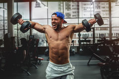 Handsome man lifting dumbbells at gym. Free weights Stock Photo