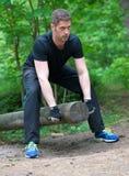 Handsome man lifting log. Royalty Free Stock Photos
