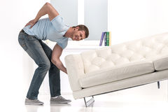 Handsome man lifting sofa and feeling pain. Royalty Free Stock Photography