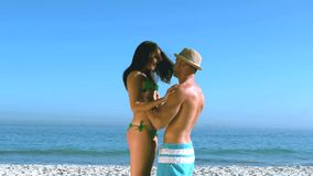 Handsome man lifting up his pretty girlfriend. Then turning with her on the beach in slow motion stock video footage
