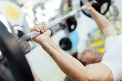 Handsome man lifting weights in gym stock photos