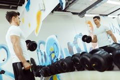 Handsome man lifting weights in gym royalty free stock photo