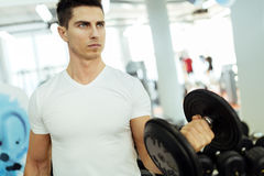 Handsome man lifting weights in gym. And staying fit Royalty Free Stock Photos