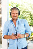 Handsome man in the light blue shirt posing with headphones and Stock Photo