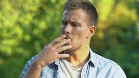 Handsome man lighting cigarette and inhaling bitter smoke, resting outdoor
