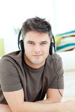Handsome man listening music lying on the floor Stock Images