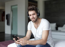 Handsome man listening music on tablet by earphones Stock Photography