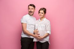 Handsome man is listening to his beautiful pregnant wife`s tummy and smiling Stock Photos