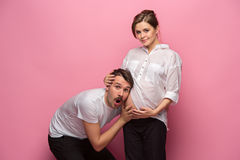 Handsome man is listening to his beautiful pregnant wife`s tummy and smiling Royalty Free Stock Image