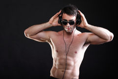 Handsome man listening to music on headphone Stock Photos