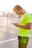 Handsome man listening to music on headphones on smart phone while resting Stock Images