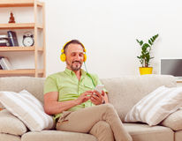 Handsome man listening to music at home Stock Photography