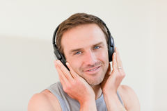 Handsome man listening to some music. In his bedroom Stock Photos