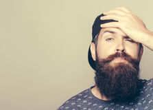 Handsome man with long beard. Tired attractive young man in cap with long beard and moustache Royalty Free Stock Photography