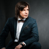 Handsome man with long hair brunette and brown eyes in dark suit. With stripes and bow tie sitting and looking forward at black background Royalty Free Stock Image