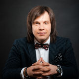Handsome man with long hair brunette and brown eyes dark suit wi. Th stripes and bow tie sitting and looking forward at black background Royalty Free Stock Image