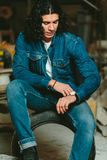 Handsome man with long hair brunette in a denim jacket stock photo