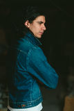 Handsome man with long hair brunette in a denim jacket Royalty Free Stock Photo