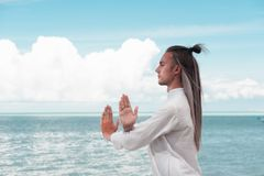 Handsome man is practicing Taijiquan on the beach royalty free stock photos
