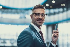 Handsome man looking aside and holding cellular in hands stock images