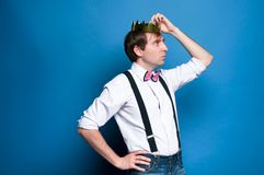 Handsome man looking away and correcting golden crown on head on blue background stock photos