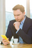 Handsome man looking concerned staring at his smartphone. Royalty Free Stock Photo
